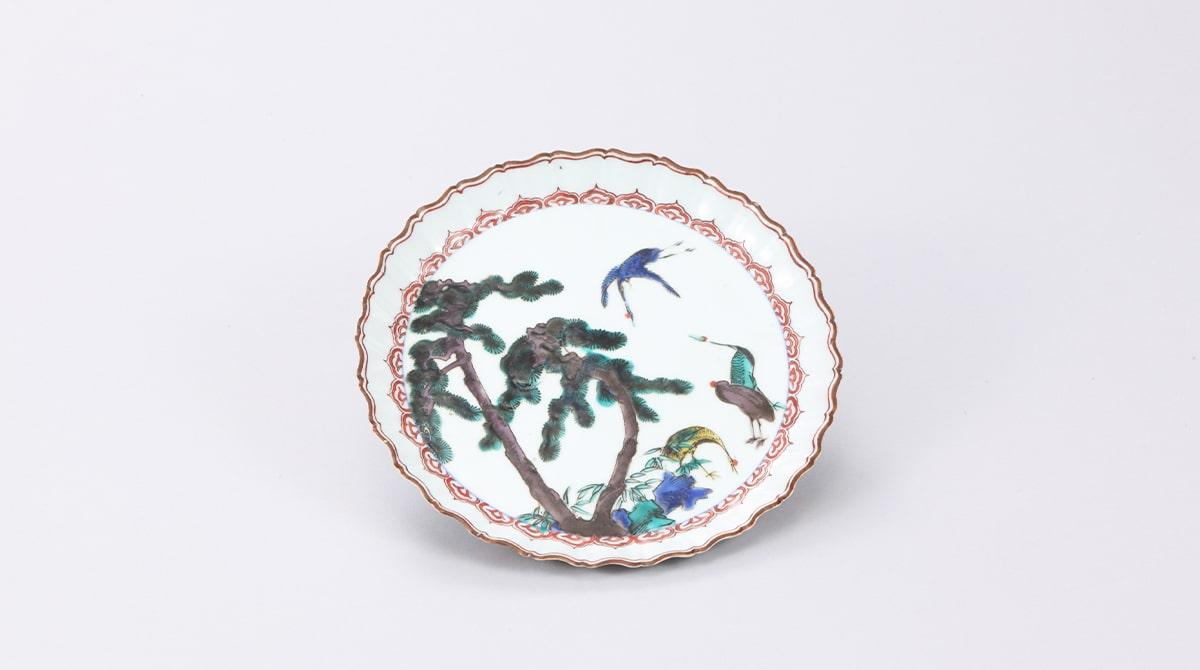 五彩で描かれた古九谷。九谷五彩という緑・黄・紫・紺青・赤の色絵の具を使用する。花鳥風月などを日本画のように余白を残して彩る。「色絵松鶴図皿」/能美市九谷焼美術館|五彩館|所蔵
